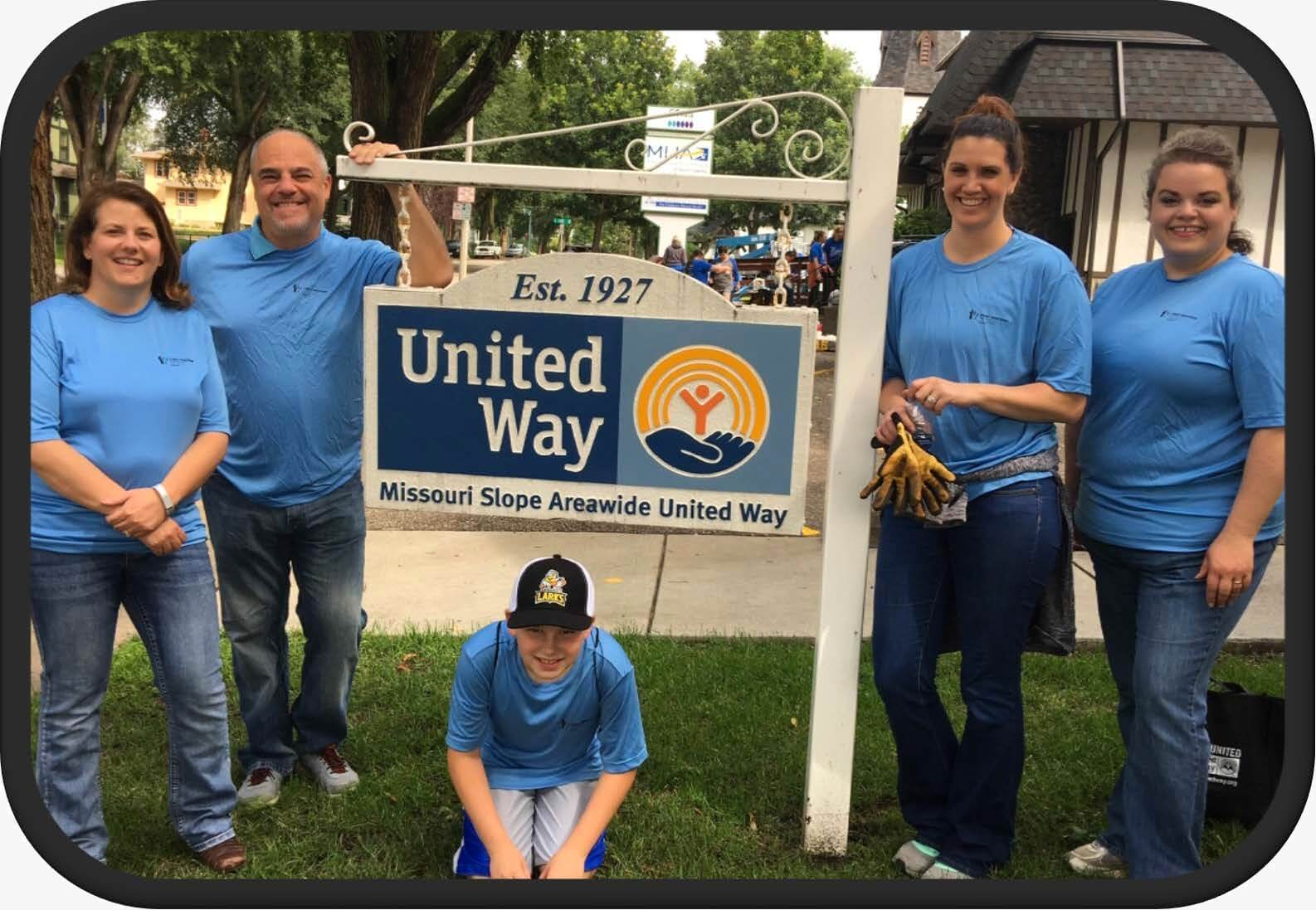 Employees standing by a United Way sign